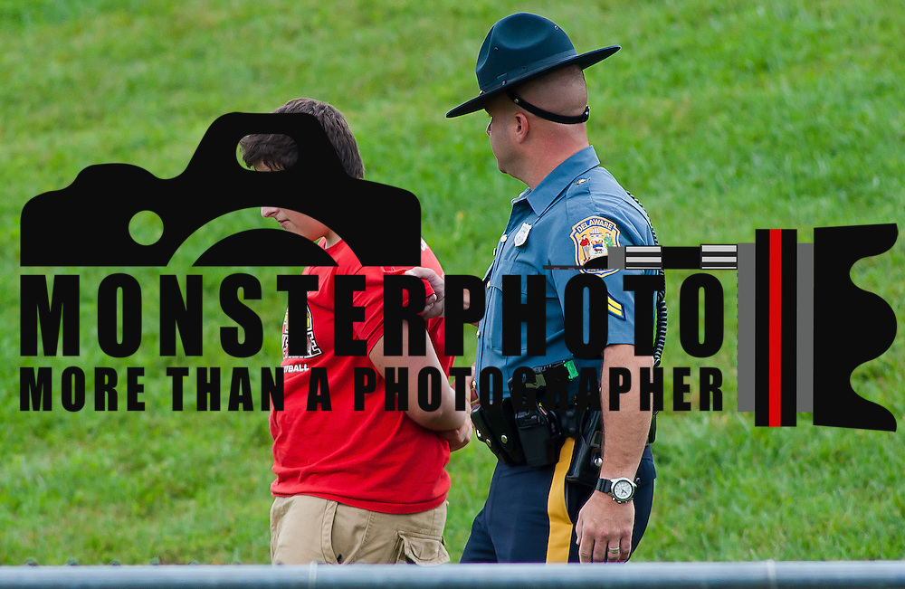 Delaware state trooper removes a fan from the stands during a Week 3 high school football game the third quarter Saturday afternoon Sept. 24, 2011 in Wilmington DE. ..The News Journal/Saquan Stimpson