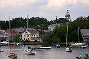 Sailboats moored along the Annapolis waterfront with the historic state capital building in the skyline.