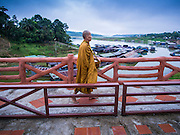 16 SEPTEMBER 2014 - SANGKHLA BURI, KANCHANABURI, THAILAND:  A Mon Buddhist monk walks over a bridge near Sam Prasob, a point where three rivers come together in Sangkhla Buri. The Mon were some of the first people to settle in Southeast Asia, and were responsible for the spread of Theravada Buddhism in Thailand and  Indochina. The Mon homeland is in southwestern Thailand and southeastern Myanmar (Burma). The Mon in Thailand traditionally allied themselves with the Thais during the frequent wars between Burmese and Siamese Empires in the 16th - 19th centuries and the Mon in Thailand have been assimilated into Thai culture. The Mon in Myanmar were persecuted by the Burmese government and many fled to Thailand. Sangkhla Buri is the center of Burmese Mon culture in Thailand because thousands of Mon came to this part of Thailand during the persecution.   PHOTO BY JACK KURTZ