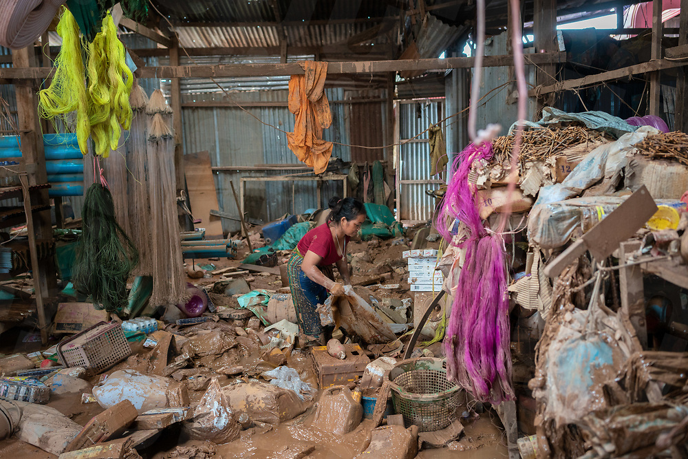 August 05, 2018 - Attapeu (Laos). Sovampheng (38) tries to save some of the goods from a tick layer of mud that covered her shop, in the small village of Kokkong, on the edge of area affected by the floods. Her family has to spend several nights on the rooftop of their house after some people tried steal what remains of their goods. Kokkong village has been partially submerged by the floods but most of the houses are covered in mud but still in good condition. © Thomas Cristofoletti / Ruom