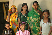 Bachau and Mishri Yadav's oldest child, daughter Nishadevi, 19, called Guddi, and sisters Aarti and Seema pose for a portrait with their mother's sister, Soni, visiting from a nearby village, and another family friend. Ahraura Village, Uttar Pradesh, India. Revisit with the family, 2004. The Yadavs were India's participants in Material World: A Global Family Portrait, 1994 (pages: 64-65), for which they took all of their possessions out of their house for a family-and-possessions-portrait.