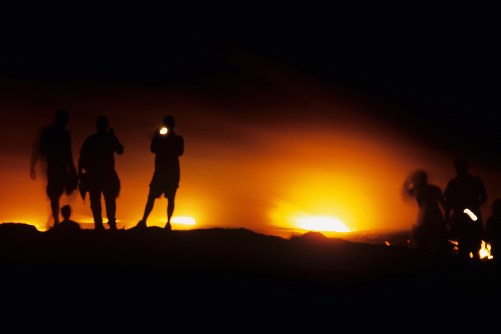 USA, Hawaii, Volcanoes National Park,  Tourists lit by flames as lava burns Chain of Craters Road during Kilauea eruption at night
