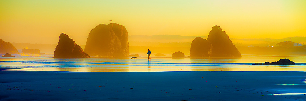 A man walks his dog on the beach at sunrise in Bandon, Oregon