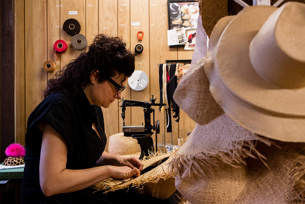 Hand sewing the finishing touches on the sweatband of a straw hat. Behind Cha Cha is an old chain-stitch sewing machine with a high arch and a short, narrow free arm, ideal for reaching into the crowns of hats.