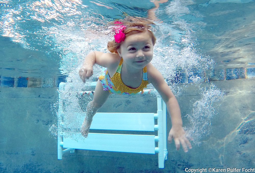 July 23, 2014 –  Three-year-old Isla Whidden learns to swim on Wednesday.  Karen Packer teaches water survival skills, to infants and children at her Collierville home. It provides them with the skills to help them save themselves in the event of a water accident.  (Karen Pulfer Focht/ The Commercial Appeal)