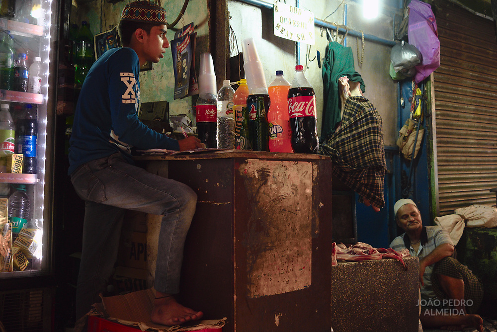 A soft drinks stand in a dark alley of Old Delhi, side by side with a street butcher.