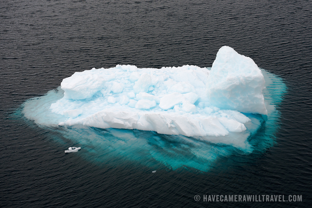 "A small iceberg, with a sizeable amount under the water, sits on the waters of the Lemaire Channel on the western side of the Antarctic Peninsula. The Lemaire Channel is sometimes referred to as ""Kodak Gap"" in a nod to its famously scenic views."