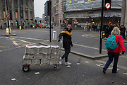 An Evening Standard newspaper vendor pulls a trolley of copies over Bank Triangle junction, on 9th February 2017, in the City of London, England.