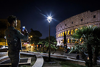 ROME, ITALY - 20 MARCH 2017: A man photographs the Colosseum by a white light LED lamppost (center, foreground), while the background is lit by yellow light sodium lampposts (background, left) in Rome, Italy, on March 20th 2017.<br /> <br /> Rome is undergoing a city-wide plan to change its public illumination from the current yellow sodium street lights CK to white LED lamps. In making the change, Rome joins a long line of cities around the world that have switched to the cheaper, and more environmentally friendly LED lighting, and it is not the first city where that change has come at the price of protest.<br /> <br /> Since July, some 100,000 led lights have already been installed, just over half the number that will be substituted in the 53 million euro changeover that is expected to save the city millions of euros in electrical bills. But when Rome's municipal electrical utility ACEA began to substitute the lamps in Rome's historic center, residents began to take note.