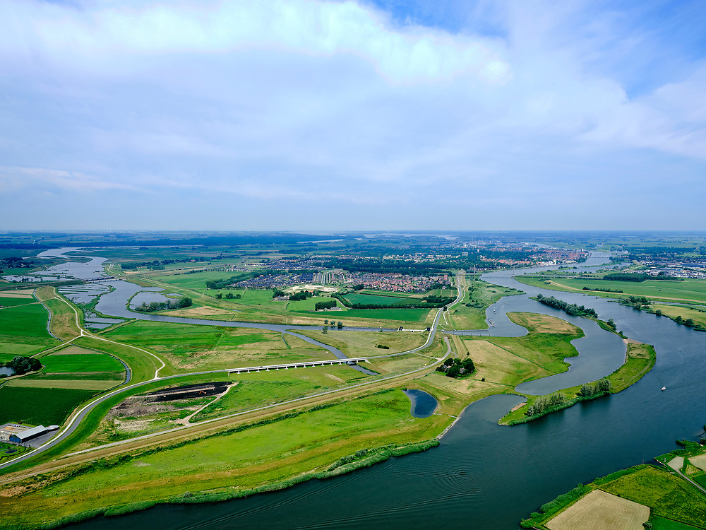"Nederland, Overijssel, Gemeente Kampen; 21–06-2020; zicht op de IJssel en de Onderdijkse Waard, Kampen in de achtergrond met het inlaatwerk van het nieuw aangelegde Reevediep, Het Lange End.<br /> Het Reevediep is aangelegd in het kader van het project Ruimte voor de Rivier om bij hoogwater water af te voeren voordat dit het nabij gelegen Kampen bereikt, direct naar het IJsselmeer, de 'bypass Kampen'. Het Reevediepgebied is ook een natuurgebied en vormt een ecologische verbindingszone tussen rivier de IJssel en Drontermeer.<br /> View of river IJssel with the Onderdijkse Waard, Kampen city in the background. The newly constructed inlet of the Reevediep, The Long End.<br /> The Reevediep has been constructed as part of the Room for the River project, and functions to discharge high waters before reaching the nearby Kampen, directly to the IJsselmeer, the ""bypass Kampen"". The Reevediep area is also a nature reserve and forms an ecological connecting zone between the river IJssel and Drontermeer.<br /> <br /> luchtfoto (toeslag op standard tarieven);<br /> aerial photo (additional fee required)<br /> copyright © 2020 foto/photo Siebe Swart"