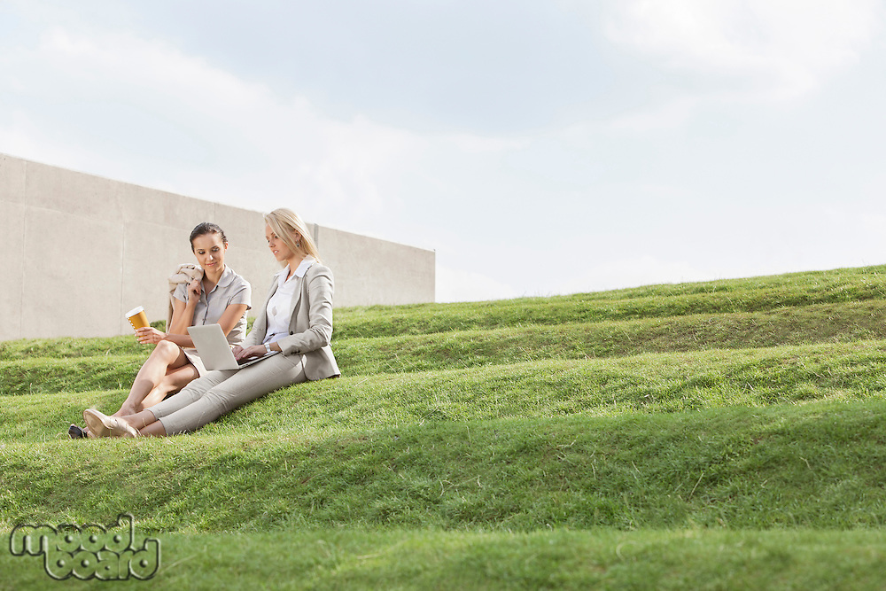 Full length of businesswomen with disposable coffee cup and laptop sitting on grass steps against sky