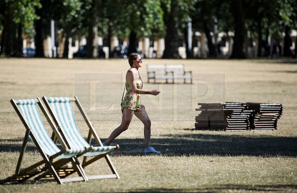 © Licensed to London News Pictures. 23/07/2018. London, UK. A young woman walks past deck chairs in St James's Park central London, as the hot weather continues in the capital. Forecasters are predicting record temperatures this week. Photo credit: Ben Cawthra/LNP