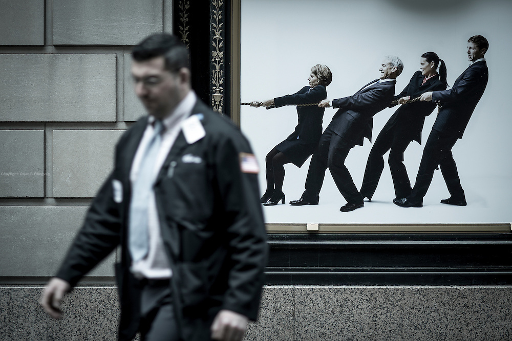 TUG OF WAR: A floor broker walks past an ad for the NYSC gym on Wall Street.
