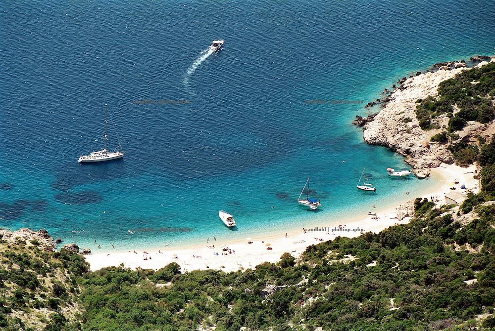 In einer Bucht auf der Kroatischen Insel Cres haben Boote und kleine Yachten festgemacht. Touristen liegen am Strand. Das für die Adria typische blaue Wasser laedt zum Baden ein...An adriatic bay in crotia growded by yachts in summer.