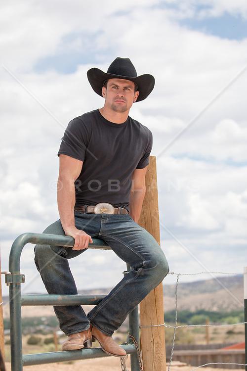 cowboy sitting on a fence