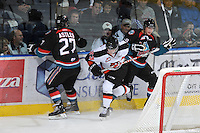KELOWNA, CANADA, OCTOBER 11:  Alex Theriau #23 of the Medicine Hat Tigers is checked between Jessey Astles #27 and Austin Ferguson #28 of the Kelowna Rockets as the Medicine Hat Tigers visited the Kelowna Rockets on October 11, 2011 at Prospera Place in Kelowna, British Columbia, Canada (Photo by Marissa Baecker/shootthebreeze.ca) *** Local Caption ***Alex Theriau;Jessey Astles;