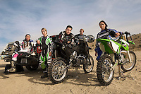 Motocross racers with bikes in desert (portrait)