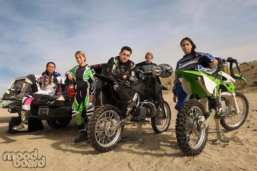 Motocross racers with bikes in desert (portrait)