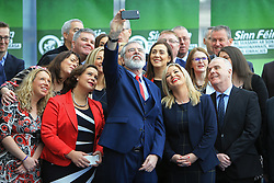 © Licensed to London News Pictures. 6/02/2016. Belfast, Northern Ireland, UK. Sinn Fein's Party President Gerry Adams does a selfie after the Launch of their Candicates for the forth coming elections in Northern Ireland. The fallout from the RHI scandal surrounding the scheme, which is approximately £490m over budget, resulted in the resignation of Sinn Fein's deputy first minister, Martin McGuinness, the collapse of Stormont's institutions and the calling of snap elections on 2 March.  Photo credit : Paul McErlane/LNP