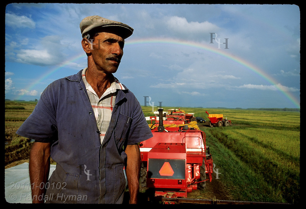 Sharecropper surveys rice field from atop combine he helped buy, framed by rainbow; Pelotas, RS. Brazil