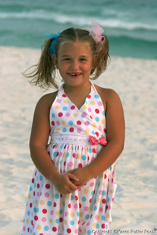 Portrait of a young girl missing a tooth on the beach.