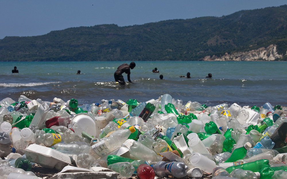 Children play on the litter-strewn beach off Jacmel