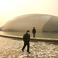 A man walk in front of the National Grand Theater in Beijing, China. The city's futuristic new national theater, containing a 2,416-seat opera house, a 2,017-seat concert hall and a 1,040-seat theater will formally open with a series of performances.in Beijing, China January 22, 2008. Photos: Bernardo De Niz