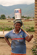 Africa. Malawi. Usisya Village..Woman carrying USA aid tin on her head..CD0010