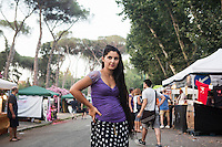 "ROME, ITALY - 3 JULY 2016: Gipsy Quen member Maria Miglescu (20) is here at the Ponte Nomentano park which hosts the iFest, an alternative music festival, where the Gipsy Queens have a food stand, in Rome, Italy, on July 3rd 2016.<br /> <br /> The Gipsy Queens are a travelling catering business founded by Roma women in Rome.<br /> <br /> In 2015 Arci Solidarietà, an independent association for the promotion of social development, launched the ""Tavolo delle donne rom"" (Round table of Roma women) to both incentivise the process of integration of Roma in the city of Rome and to strengthen the Roma women's self-esteem in the context of a culture tied to patriarchal models. The ""Gipsy Queens"" project was founded by ten Roma women in July 2015 after an event organised together with Arci Solidarietà in the Candoni Roma camp in the Magliana, a neighbourhood in the South-West periphery of Rome, during which people were invited to dance and eat Roma cuisine. The goal of the Gipsy Queen travelling catering business is to support equal opportunities and female entrepreneurship among Roma women, who are often relegated to the roles of wives and mothers."