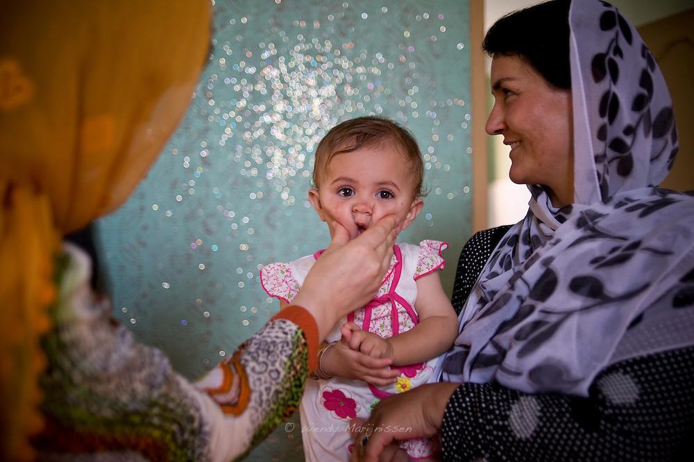 MP Ms. Fawzia Koofi plays with a child in between meetings held in her family home in Faizabad. Badakshan, Afghanistan, 2012