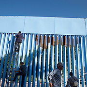 "Manuel Flores, a local Nogales Sonora native joins Artist Ana Teresa Fernández with local and some Arizonians paint the fence in blue color the theme called ""Erasing the Border"" in Nogales Sonora, Mexico on October 13, 2015."