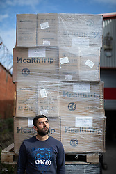 "© Licensed to London News Pictures. 07/05/2020. Salford, UK. Manager at Puro Medico SALAIMAAN MAJID (28) stands in front of remaining stock of masks stored outside the warehouse from where the PPE was stacked up when it was stolen . £166,000 (one hundred and sixty six thousand pounds) worth of protective masks , which were destined for the NHS and care homes , have been stolen from a warehouse overnight (6th-7th May 2020) in what Greater Manchester Police are describing as a "" targeted burglary "" . Thieves cut the shutters at the loading bay of Puro Medico - which specialises in importing PPE such as masks from China and hand sanitiser from Poland - and stole several pallets of stock , which was loaded on to vans over a two hour period . Photo credit: Joel Goodman/LNP"