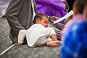 """Sept. 10 - GLENDALE, AZ:  A child sleeps in his father's lap during Eid up-Fitr prayer services in the Glendale Civic Center. Muslims from the Phoenix area celebrated Eid ul-Fitr, the end of Ramadan, at the Glendale Civic Center in Glendale, AZ, a suburb of Phoenix. Eid ul-Fitr, often abbreviated to Eid, is the Muslim holiday that marks the end of Ramadan, the Islamic holy month of fasting. Eid is an Arabic word meaning """"festivity"""", while Fitr means """"conclusion of the fast""""; and so the holiday symbolizes the celebration of the conclusion of the month of fasting from dawn to sunset during the entire month of Ramadan. The first day of Eid, therefore, is the first day of the month Shawwal that comes after Ramadan.  Photo by Jack Kurtz"""