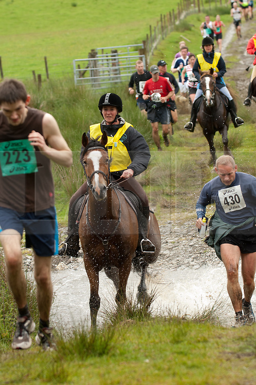 © licensed to London News Pictures.Llanwrtyd Wells, UK   11/06/2011 Runners and riders Compete in the 2011 Man vs Horse Race at Llanwrtyd Wells in mid Wales.The Race is run over a 22 mile course through a mixture of farm tracks, footpaths, forestry and open moorland.  Please see special instructions for usage rates. Photo credit should read Aled LLywelyn/LNP