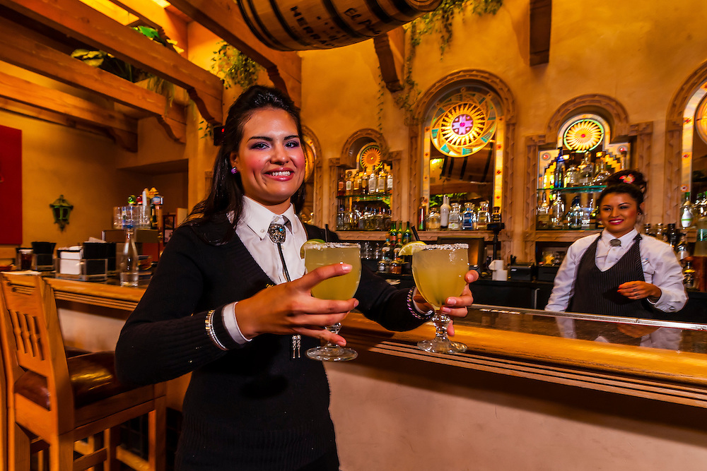 A waitress carrying margaritas in the bar of the El Pinto Restaurant and Cantina, Albuquerque, New Mexico USA
