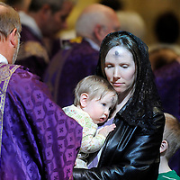 Susan Frederes holds her 8-month-old son, Dominic, after they received ashes from Deacon Roger Heidt during noon Ash Wednesday Mass at St. Joseph Cathedral in Sioux Falls, S.D.
