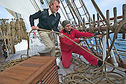 "Riggers and other crew members setting sails aboard the ""Lili Marleen"" (luxurious sailing ship of Deilmann Cruises)."