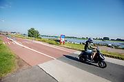 Bij Ameide rijdt een jongen op een brommer over de Lekdijk.<br /> <br /> Near Ameide a boy is riding a moped.