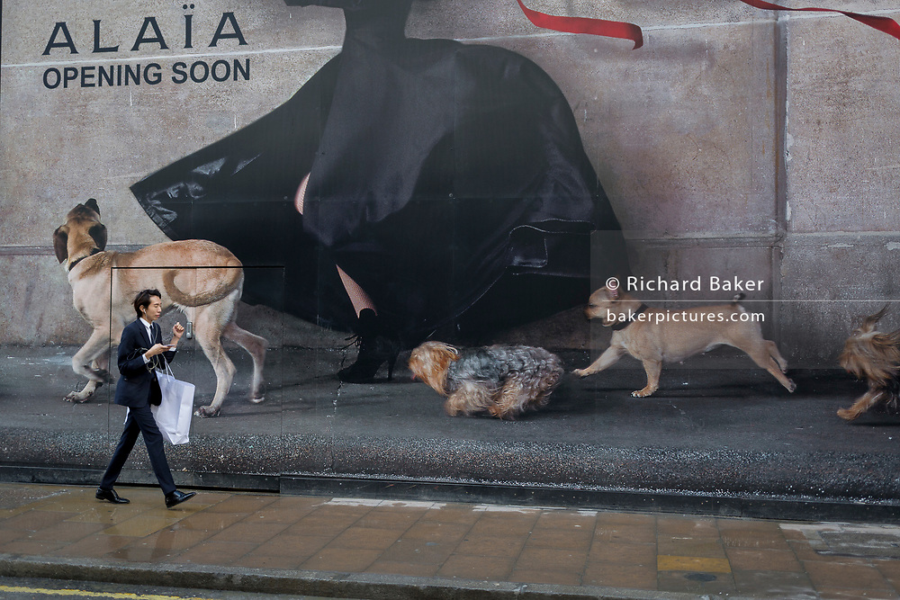 A passer-by walks beneath a large construction hoarding for Alaia on New Bond Street, on 17th January 2018 in Westminster, London, England.