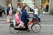 Een vrouw fietst met twee kinderen achterop door Amsterdam.<br /> <br /> A woman is cycling with two children at the back of the bike in Amsterdam.