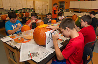 Laconia Middle School students Karter Greenwood showing Laconia spirit with his pumpkin carving in Mrs. Connelly's 7th grade Maple Team to be added to the Tower for Pumpkin Fest on Saturday.  (l-r Ethan Devos, Maximus Heath, Ryan Brouillet, Jane Connelly, Kaleb Daignealt, Ryan Steele, Peter Simeonov, Karter Greenwood) (Karen Bobotas/for the Laconia Daily Sun)