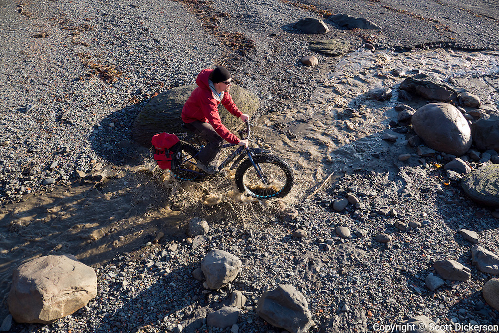 Carl Seger crosses a stream on his fat tire bike on the beach at the edge of Kachemak Bay near Homer, Alaska during an unseasonably warm winter day.