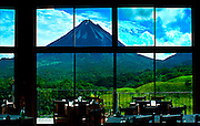 Mountain lodge restaurant windows provide dramatic views of the Arenal Volcano in El Castillo, Costa Rica.