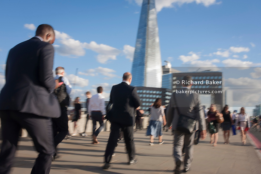 The blured movement of commuters crossing London Bridge, from the City of London to the south bank of the Thames in Southwark, England UK.