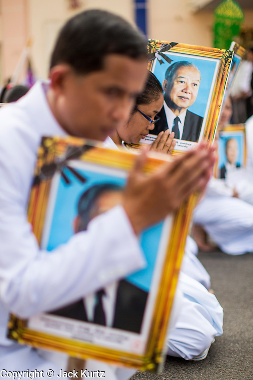 """01 FEBRUARY 2013 - PHNOM PENH, CAMBODIA:  Mourners carry photos of former Cambodian King Norodom Sihanouk as they follow his funeral procession through Phnom Penh. Norodom Sihanouk (31 October 1922- 15 October 2012) was the King of Cambodia from 1941 to 1955 and again from 1993 to 2004. He was the effective ruler of Cambodia from 1953 to 1970. After his second abdication in 2004, he was given the honorific of """"The King-Father of Cambodia."""" Sihanouk died in Beijing, China, where he was receiving medical care, on Oct. 15, 2012. His cremation is will be on Feb. 4, 2013. Over a million people are expected to attend the service.   PHOTO BY JACK KURTZ"""