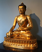 Seated Buddha, Chinese, 1740-1786,  is shown just before his enlightenment.  Gilded copper.