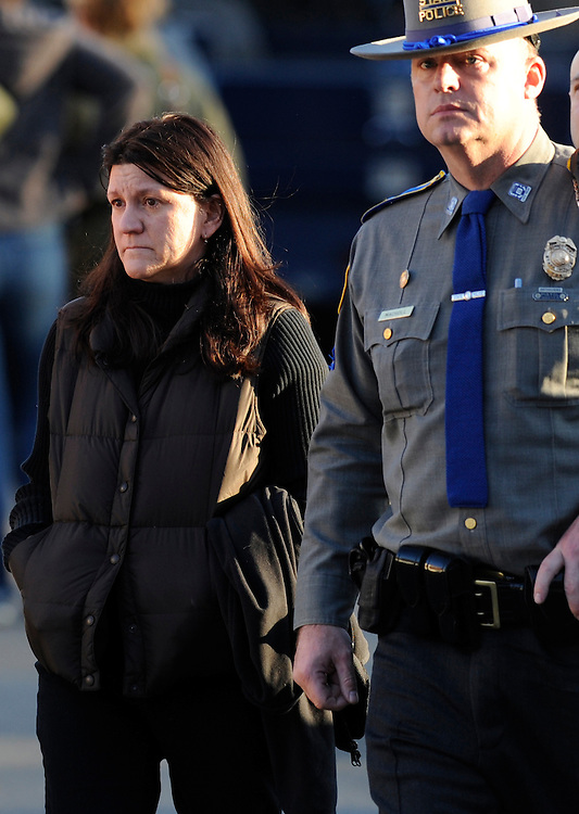 Jennifer Hensel is escorted by a Connecticut State Police trooper outside a staging area near Sandy Hook Elementary School in Newtown, Conn., Friday, Dec. 14, 2012. Hensel's daughter, Avielle Rose Richman, was one of 20 children killed in the shooting. (AP Photo/Jessica Hill)