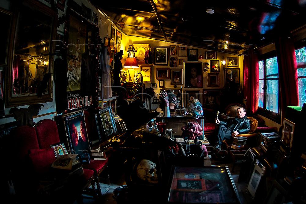 """Jacques Sirgent dans son musée.<br /> Paris, avril 2017.<br /> «Nous avons toujours été un pays de légendes, il serait temps de l'assumer.»<br /> Jacques Sirgent, auteur né au Canada de parents français est depuis toujours un passionné des thèmes liés au vampirisme. Il a fondé le musée des vampires et monstres de l'imaginaire à Paris.On dit de lui qu'il est le 1er """"vampirologue"""" au monde.Après un passage un jardin qui se charge de vous mettre dans l'ambiance (graffitis mystiques, pierres tombales, squelettes et totems d'animaux fantastiques accrochés aux arbres, certains le disent hanté) on découvre le musée, composé d'une seule pièce.Ancien atelier de sculpture du père de Jacques Sirgent, l'endroit rassemble des centaines d'objets sur le mythe du vampire.<br /> <br /> Cette collection personnelle donne des frissons : chauve-souris conservée sous verre, rangées de livres anciens sur le Mal, tableaux, poupées, et quelques bizarreries sympathiques comme cette arbalète anti-vampire ou encore cet authentique kit de protection contre les vampires datant du XIXe siècle… Quelques pièces collector, aussi : la machine à écrire de Bram Stoker, le mythique auteur de Dracula, ou des affiches dédicacées de tous les acteurs qui ont interprété le vampire au cinéma.<br /> Le musée possède une bibliothèque dont certains ouvrages remontent au XVIIesiècle et qui se compose de plus de 1500 ouvrages<br /> Si vous êtes émotif, évitez la visite par une nuit sans lune."""