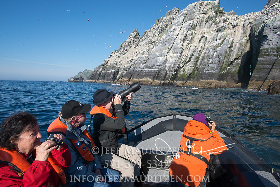 Expedition tourists takes photos of the seabird colony on the island of Little Skellig, Ireland.