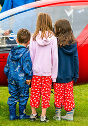 Pictured: Scotland's National Airshow, East Fortune, East Lothian, Scotland, United Kingdom, 27 July 2019 . A packed programme of aircraft old and new planned to take to the skies for the aerial display was marred by poor weather at airfields around the country which meant that many of the promised flights were unable to perform. Children admire a micrilight.<br /> Sally Anderson | EdinburghElitemedia.co.uk